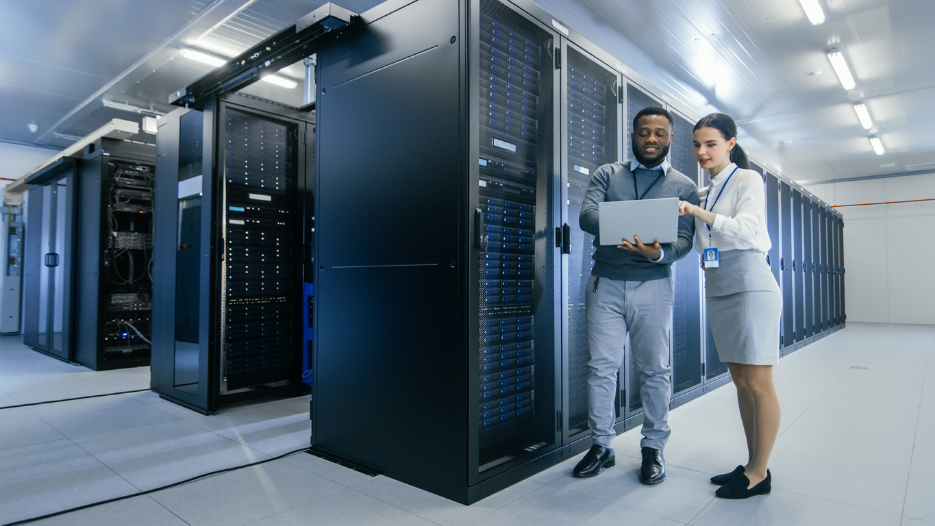 A man and a woman standing in a data center and looking at a tablet as they explore ways to stop a data center system failure