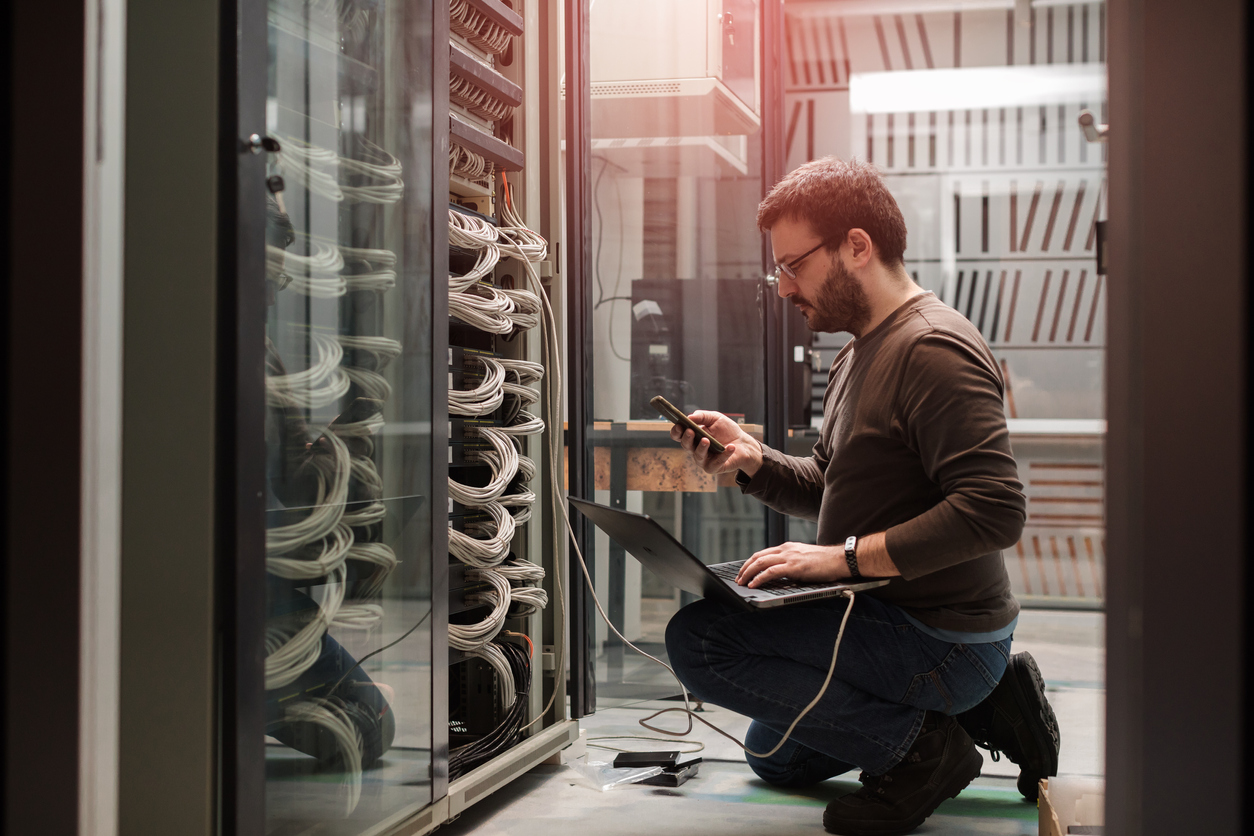 IT professional evaluating the condition of servers in an server room