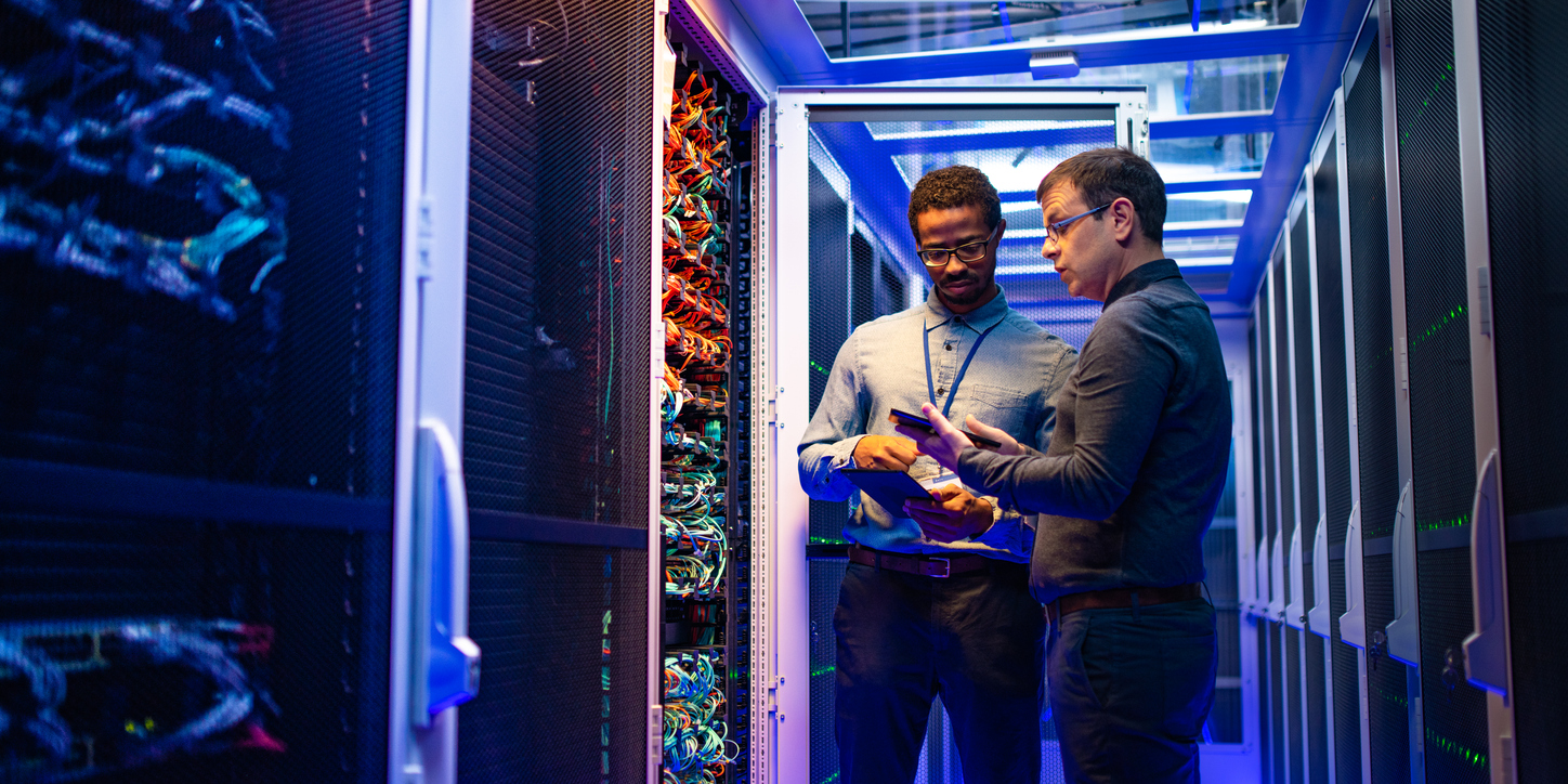 Two male IT engineers standing in front of a collection of wires in the middle of a data center
