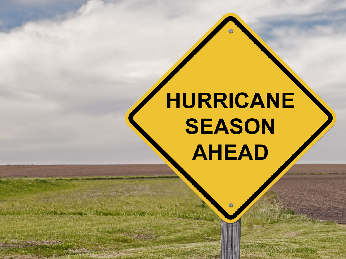 """Yellow caution sign that reads """"Hurricane Season Ahead"""" in the foreground and a blue sky and clouds in the background"""