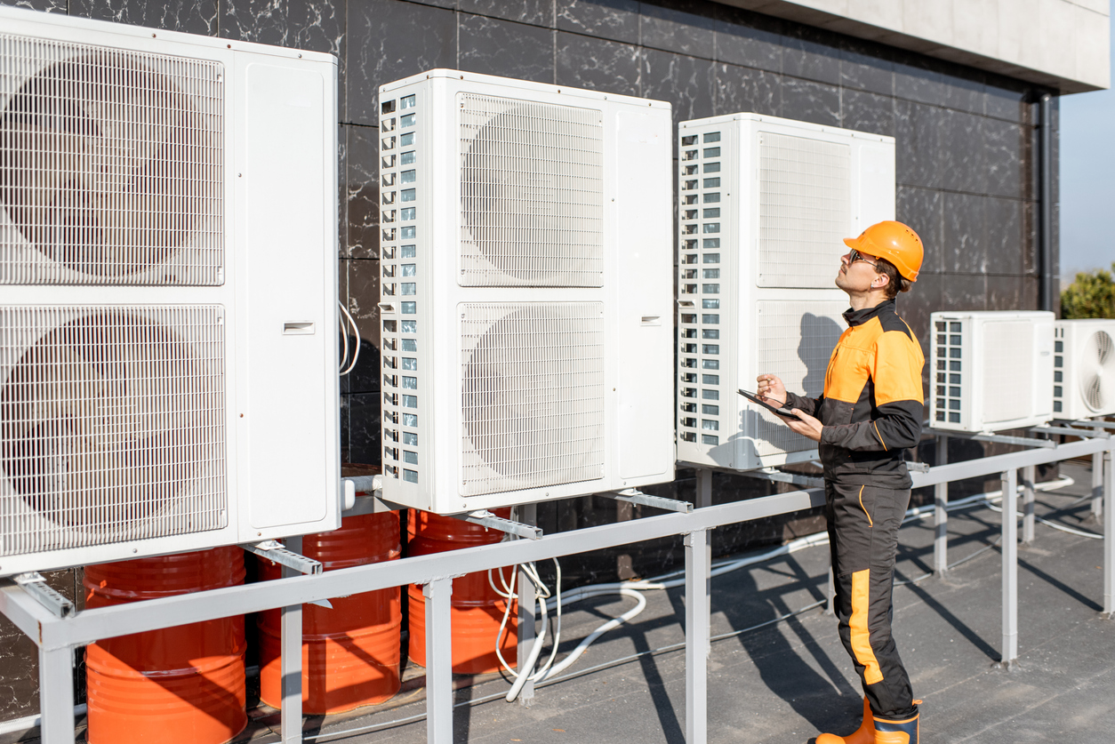 Commercial electrical services professional in protective clothing holding a tablet and evaluating an HVAC system