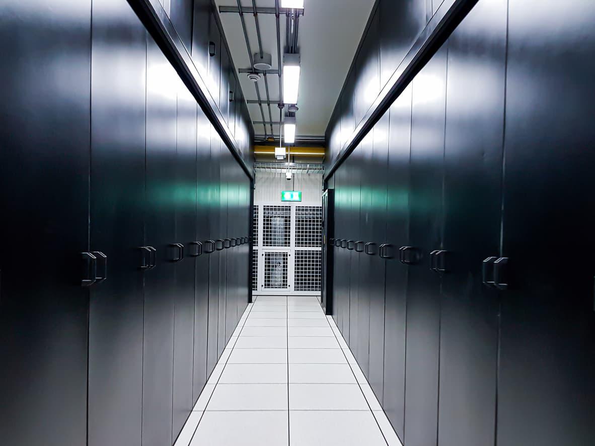 A walkway between racks of databanks in a data center.